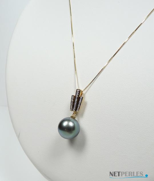 Gros plan sur un bijou en Or jaune 18 carats avec ses diamanrts et une perle noire de tahiti
